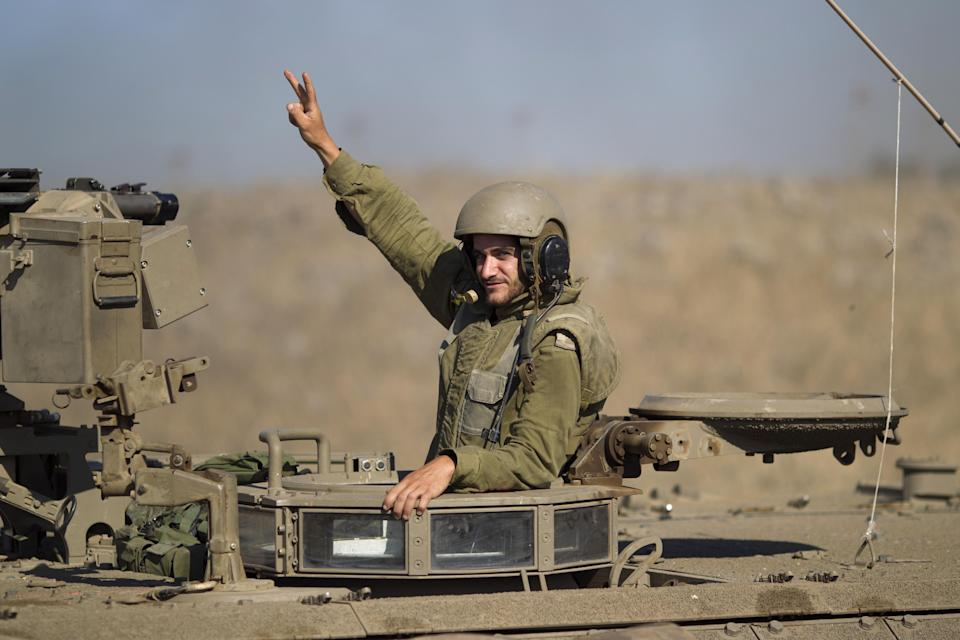 An Israeli officer from the Golani brigade waves from an APC (Armored Personnel Carrier) during a military exercise in the Israeli-controlled Golan Heights near the border with Syria, Tuesday, June 25, 2013. (AP Photo/Ariel Schalit)