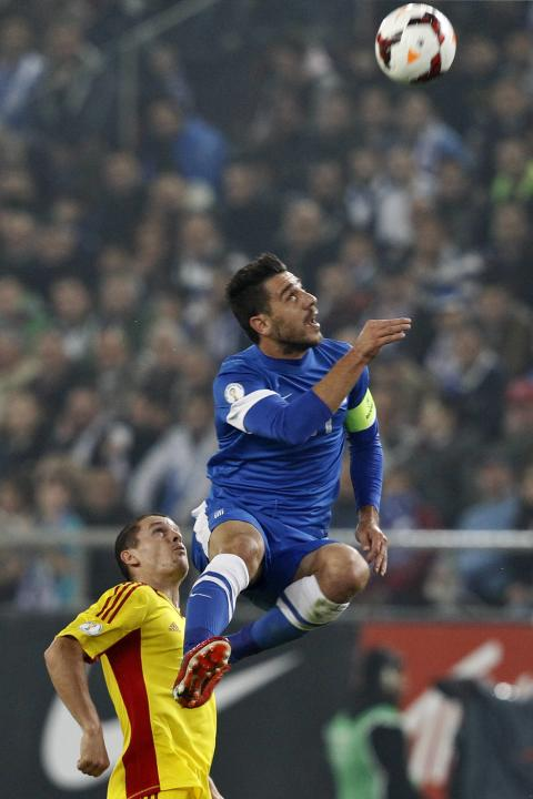 Greece's Kostas Katsouranis jumps for the ball against Romania's Alexandru Bourceanu during their 2014 World Cup qualifying playoff first leg soccer match at Karaiskaki stadium in Piraeus