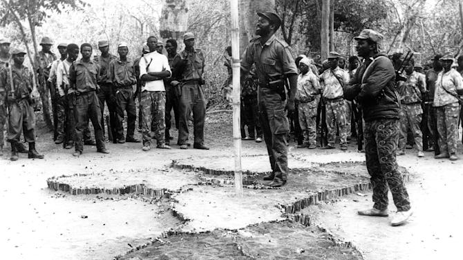 FILE: 1974 file photo shows  Samora Machel, centre, wearing military style dress and pistol holster, addresses Frelimo guerilas in Cabo Delgado, Mozambique.  South African police said Wednesday Dec. 12, 2012  they've opened a new investigation into the 1986 airplane crash that killed Mozambique's Marxist president Machel, an incident that many have blamed the former apartheid government.  (AP Photo/Str-FILE)