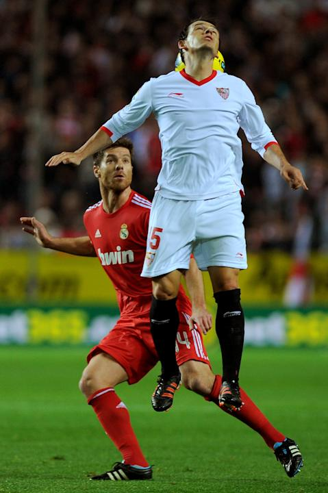 Real Madrid's midfielder Xabi Alonso (L) vies for the ball with Sevilla's Polish midfielder Piotr Trochowski (R) during their Spanish league football match Sevilla FC vs Real Madrid on December 17, 20