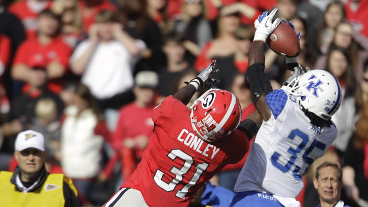 Kentucky cornerback Cartier Rice (35) catches an interception on a pass intended for Georgia wide receiver Chris Conley (31) during the second quarter of an NCAA college football game Saturday, Nov. 19, 2011 in Athens, Ga. (AP Photo/David Goldman)