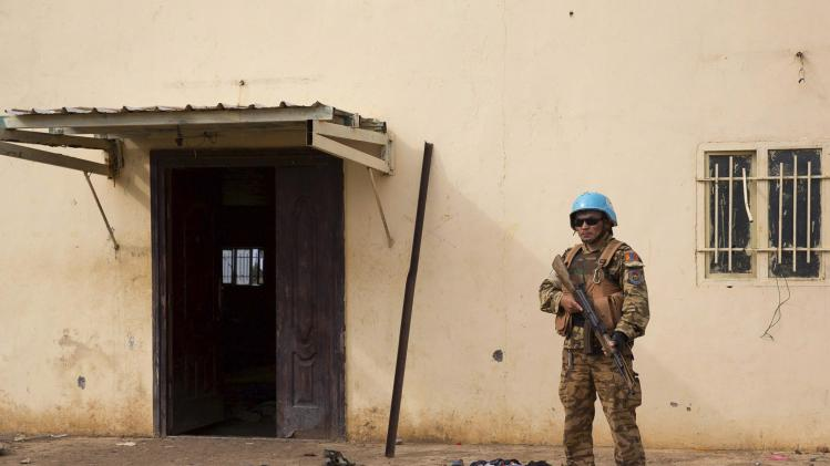 A United Nations peacekeeper stands guard near the scene where about 200 people were killed during an attack in Bentiu