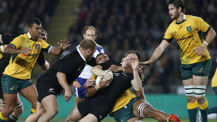 Smith of New Zealand's All Blacks is tackled around the neck by Palu of Australia's Wallabies during their Bledisloe Cup rugby championship match in Auckland