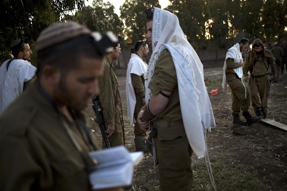 Israeli soldiers of the Golani brigade, few covered in prayer shawls, gather for the morning prayer before a military exercise in the Israeli controlled Golan Heights, near the border with Syria, Tuesday, May 7, 2013. (AP Photo/Ariel Schalit)