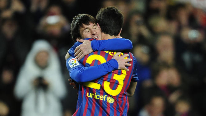FC Barcelona's Lionel Messi, from Argentina, left, reacts after scoring with his teammate Isaac Cuenca against Granada during a Spanish La Liga soccer match at the Camp Nou stadium in Barcelona, Spain, Tuesday, March 20, 2012. (AP Photo/Manu Fernandez)