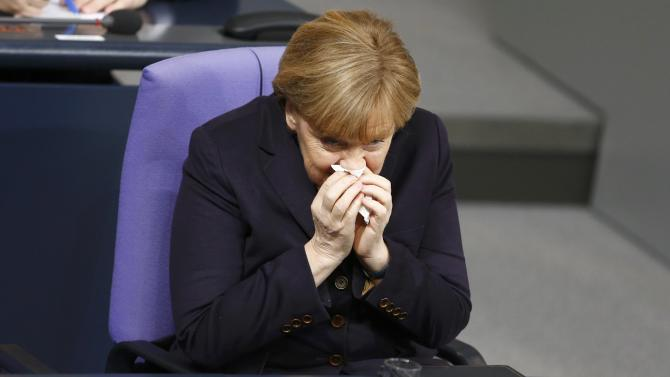 German Chancellor Merkel clears her nose during a session of the German lower house of parliament Bundestag in Berlin