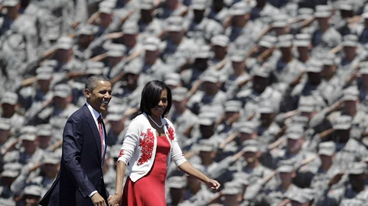 In this April 27, 2012 file photo, President Obama and first lady Michelle Obama are saluted by soldiers as they arrive at the Fort Stewart Army post in Fort Stewart, Ga. (AP Photo/David Goldman, File)