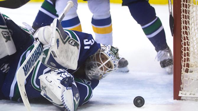 Vancouver Canucks' goalie Eddie Lack, of Sweden, watches the puck after stopping St. Louis Blues' Jaden Schwartz during the first period of an NHL hockey game in Vancouver, British Columbia, on Sunday March 1, 2015. (AP Photo/The Canadian Press, Darryl Dyck)