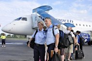 Australian Federal Police officers pose for photos before boarding a jet home, at Dili airport, on December 15, 2012 as the last batch of Australian officers under the UN police leave Asia's youngest nation