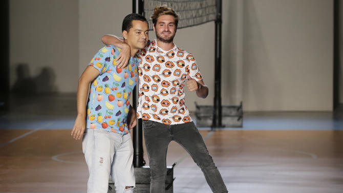 Fashion designers Diego Marquez, left, and Mirko Fontana acknowledge the applause at the end of their Au Jour Le Jour women's Spring Summer 2015 collection, part of the Milan Fashion Week, unveiled in Milan, Italy, Sunday, Sept. 21, 2014. (AP Photo/Antonio Calanni)