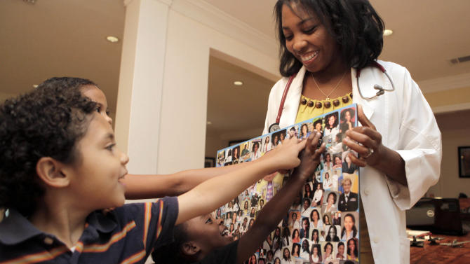 """This June 7, 2012 photo shows Dr. Myiesha Taylor, right, holding a collage of fellow doctors supporting Disney Junior's animated series """"Doc McStuffins"""" as her three children from left, Ian Taylor Schlitz, 6, Haley Taylor Schlitz, 9, and Hana Taylor Schlitz point at their mother's photo at their home in Keller, Texas. For black women whose own wish to practice medicine come true, the show is welcome affirmation. The doctors shown in the collage are graduates of schools including Harvard, Yale and Stanford and work in a range of specialities such as neurosurgery, orthopedic surgery and psychiatry. Taylor is a board-certified emergency room physician. (AP Photo/LM Otero)"""