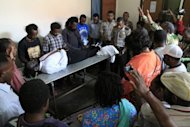 Supporters pray over the body of Mako Tabuni at a hospital in Abepura on June 15. Tabuni's supporters told Australian media he was gunned down by officers from Detachment 88, a counter-terrorism squad formed after the 2002 Bali bombings and partly trained and resourced by Australia