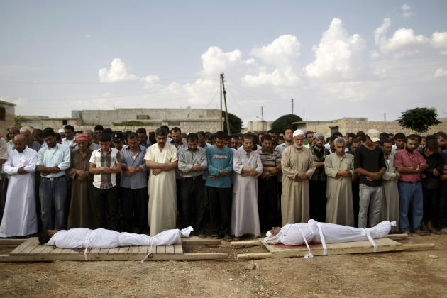 Relatives and mourners of Abdullah Alrayzar, 23, left, and Mohammed Abdul Samee, 35, pray during a funeral for four men, who were killed in a government airstrike in Marea, on the outskirts of Aleppo,
