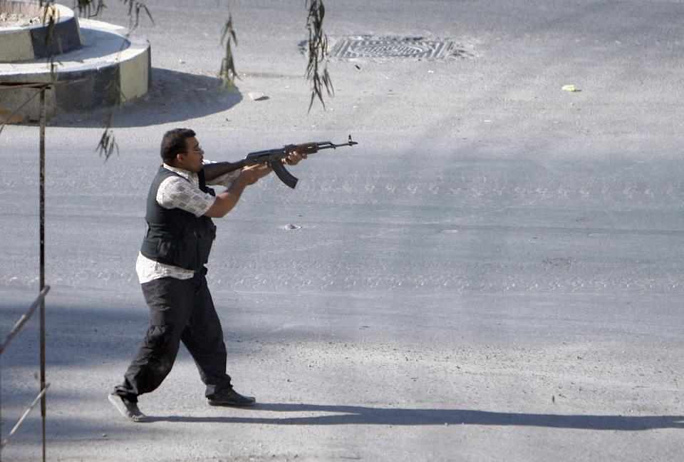 In this Thursday Aug. 2, 2012 photograph, a Syrian rebel fighter fires at an approaching car at an improvised checkpoint in a suburb of Damascus, Syria. (AP Photo)