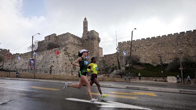 Runners are seen passing the Tower of David during the second annual marathon in Jerusalem, Friday, March 16, 2012.  About 15,000 runners, including 1,500 from overseas, are competing Friday, with some 1,000 competitors expecting to complete the full 42 kilometers (26.2 miles) marathon distance, and others aiming to complete shorter distances, including Mayor Nir Barkat who says he plans to run half a marathon and 77-year old Hanoch Shahar aiming for 10Km.  (AP Photo/Sebastian Scheiner)