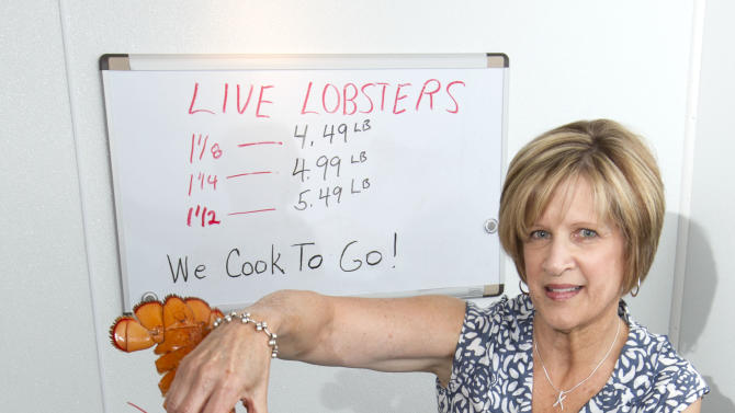 FILE-In this file photo made Thursday, June 28, 2012, Paula Coppersmith poses with a lobster at Dock's Seafood restaurant and market in South Portland, where they were selling five lobsters for $24. State officials say Maine's lobster catch surged 18 percent in 2012 for another record, but a summer glut caused the value of the state's signature seafood to drop. (AP Photo/Robert F. Bukaty, file)