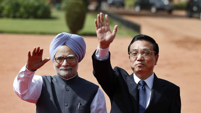 Chinese Premiere Li Keqiang, right, and Indian Prime Minister Manmohan Singh wave during Li's ceremonial reception at the Presidential Palace in New Delhi, India, Monday, May 20, 2013. Just weeks after a tense border standoff, China's new premier visited India on Sunday on his first foreign three-day trip as the neighboring giants look to speed up efforts to settle a decades-old boundary dispute and boost economic ties. (AP Photo/Saurabh Das)