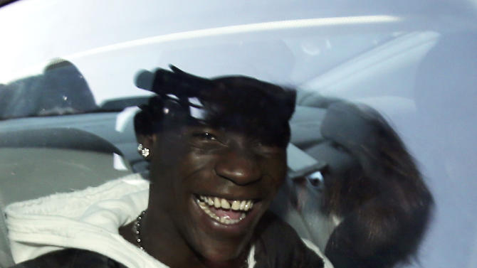 "Mario Balotelli smiles as he arrives in Busto Arsizio, near Varese, Italy, for medical checks, Wednesday, Jan. 30,  2013. AC Milan announced on Tuesday that it has reached an agreement with Manchester City to sign Italy striker Mario Balotelli from the English champions. City declined to comment on reports that a deal had been struck for the 22-year-old forward, who joined the Premier League club from Milan's city rival Inter in 2010. ""An agreement has been reached with Manchester City, Balotelli will have a medical tomorrow and then sign,"" Milan director Umberto Gandini told The Associated Press. ""If he doesn't pass the medical, it won't happen."" (AP Photo/Antonio Calanni)"