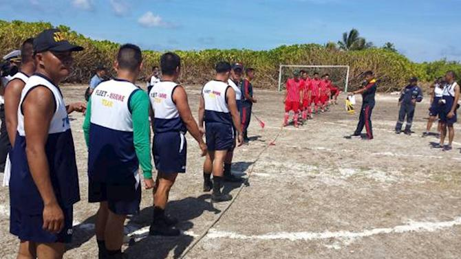 Filipino and Vietnamese troops stands at attention before the start of their tug-of-war during their Friendship Games at Northeast Cay