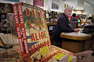 Canadian author Alice Munro's books sit on the bookshelf as her former husband Jim stands at the front counter at Munro's Bookstore in Victoria, British Columbia October 10, 2013. REUTERS/Andy Clark
