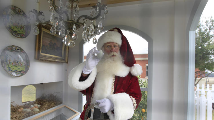 Santa Clause, portrayed by Brady White, gathers an egg from the Heritage Hen House Mini Farm on display during the unveiling of the Neiman Marcus 2012 Christmas Book in Dallas, Tuesday, Oct. 9, 2012. The Versailles-inspired Le Petit Trianon house including the chandelier in the hen house is priced for sale at $100,000.  (AP Photo/LM Otero)