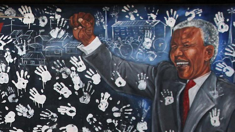 A young girl plays in front a mural depicting former South African President Nelson Mandela at the Alexandra township in Johannesburg, South Africa, Tuesday, July 17, 2012, to honor Mandela's 94th birthday which was celebrated Wednesday, July 18, 2012. (AP Photo/Themba Hadebe)