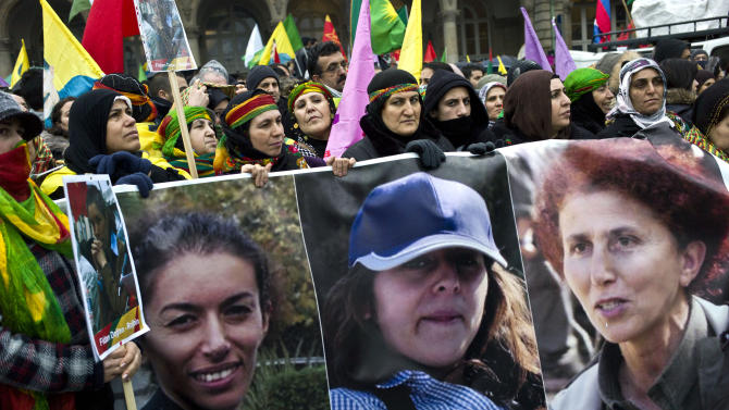 Women hold a banner displaying the three Kurdish women activists killed in Paris, during a demonstration gathering people of Kurdish origin, in Paris, Saturday, Jan. 12, 2013. (AP Photo/Thibault Camus)