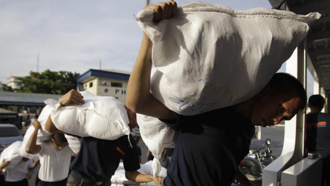 Members of the Philippine Coast Guard carry relief goods for victims of flash floods caused by Typhoon Bopha in Davao province, while loading their ship in Manila, Philippines on Thursday, Dec. 6, 2012. The powerful typhoon that washed away emergency shelters, a military camp and possibly entire families in the southern Philippines has killed hundreds of people with nearly 400 missing, authorities said Thursday. (AP Photo/Aaron Favila)