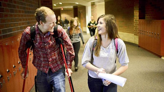 "Zach Sobiech, left, walks with his girlfriend, Amy Adamle, between classes at Stillwater High School in Stillwater, Minn., on Dec. 3, 2012. ""She's strong enough to share the load with me, said Sobiech. Sobiech, the Lakeland, Minn. teenager whose song ""Clouds"" became an Internet sensation, died early Monday, May 20, 2013 at his home, surrounded by family and his girlfriend, according to a CaringBridge post by Zach's mother. He was 18. Sobiech, who had a rare form of bone cancer, began writing songs of farewell to family and friends last fall. His first song, ""Clouds,"" went viral and has received almost 3 million hits on YouTube. (AP Photo/St. Paul Pioneer Press, Ben Garvin)"