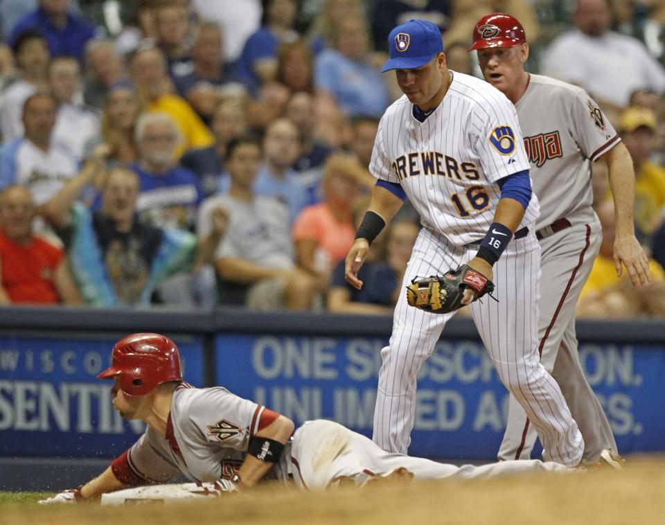 Arizona Diamondbacks' Aaron Hill, left, slides into third base for a triple as Milwaukee Brewers' Aramis Ramirez (16) looks on during the sixth inning of a baseball game on Friday, June 29, 2012, in Milwaukee.  (AP Photo/Jeffrey Phelps)