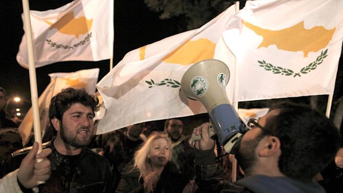 """Protesters chant slogans and wave Cypriot flags outside the Cypriot parliament, Friday, March 22, 2013. Cypriot authorities were putting the final touches Friday to a plan they hope will convince international lenders to provide the money the country urgently needed to avoid bankruptcy within days. """"The next few hours will determine the future of this country,"""" said government spokesman Christos Stylianides.(AP Photo/Petros Giannakouris)"""