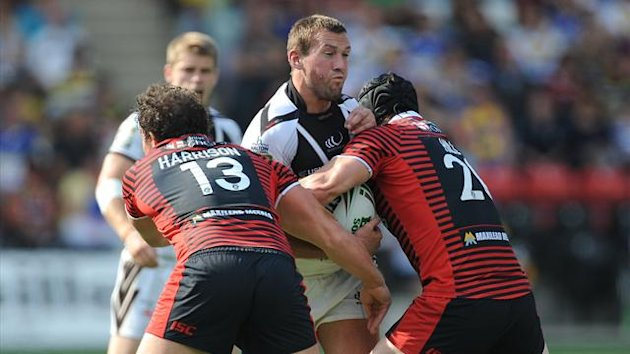 Widnes Vikings' Steve Pickersgill is tackled by Warrington Wolves' Ben Harrison (left) and Chris Hill (right) (PA)
