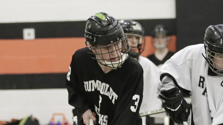 In this Jan. 29, 2013 photo, Jordan Anderson lines up for a face off during a floor hockey game between the home  Humboldt High School Hawks and the Rochester Raiders in St. Paul, Minn. Jordan, a junior with epilepsy and a developmental disability, is happy just to be able to compete in one of his favorite sports, one of several that Minnesota offers for disabled athletes. While the federal government pushes schools to include more students like Anderson in sports, Minnesota offers a map for how to do it and the limits.  (AP Photo/Jim Mone)