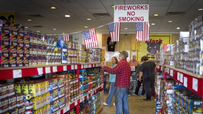 FILE - In this Friday, June, 28, 2013, file photo, people shop fireworks at Pyro City retail store, in Winslow, Maine. The government reports on sales at U.S. retailers in June on Monday, July 15, 2013. (AP Photo/Robert F. Bukaty)