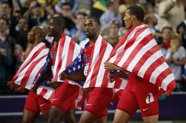 From left, United States' 4x100-meter relay team Trell Kimmons, Justin Gatlin, Tyson Gay and Ryan Bailey walk on the track taking the silver medal during the athletics in the Olympic Stadium at the 20
