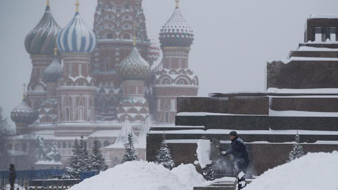A municipal worker cleans up a snow at the Red Square, with the St.Bazil's Cathedral in the background in downtown Moscow, Russia, Dec. 25, 2014. A massive snowstorm in Moscow on Thursday caused delays to more than a hundred flights and brought traffic to a standstill. (AP Photo/Pavel Golovkin)