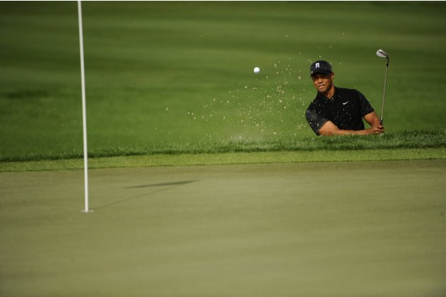 Tiger Woods of the U.S. gets out of the bunker on the 9th hole during the third round of play in the Honda Classic PGA golf tournament in Palm Beach Gardens