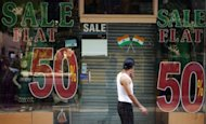 An Indian resident walks past a closed shop at Lajpat Nagar market in New Delhi in September. The Asian Development Bank has slashed its growth estimates for the region&#39;s emerging economies to the lowest level since 2009, citing a slowdown in powerhouses China and India