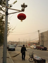 "A Chinese road sweeper works under a surveillance camera watching Ai Weiwei's studio in Beijing. The dissident Chinese artist was barred from a hearing Wednesday challenging a multi-million-dollar tax order against a firm he founded, he said, accusing authorities of trying to ""crush"" him"