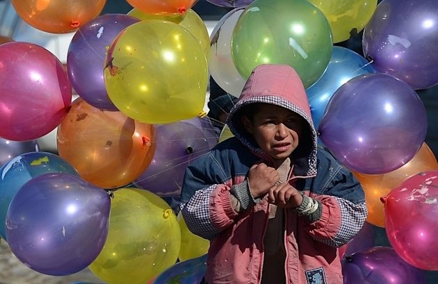 An Afghan boy is seen with balloons, on a cold winter's day in Kabul, on February 7 , 2013