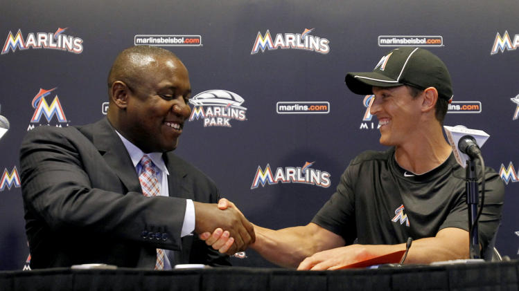 Adam Greenberg, right, and Miami Marlins general manager Michael Hill shake hands after Greenberg signed a one-day contract before a baseball game against the New York Mets in Miami, Tuesday, Oct. 2, 2012. Greenberg was beaned in his debut for the Chicago Cubs in 2005. He never made it to the big leagues again. Until now, at 31. (AP Photo/Alan Diaz)