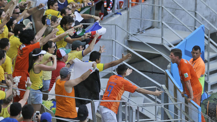 Netherlands' Klaas-Jan Huntelaar, right, celebrates with fans after scoring his side's second goal from the penalty spot during the World Cup round of 16 soccer match between the Netherlands and Mexico at the Arena Castelao in Fortaleza, Brazil, Sunday, June 29, 2014. Holland won 2-1 and advanced to the quarterfinal. (AP Photo/Themba Hadebe)
