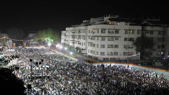 In this Sunday, Nov. 18, 2012 photo, people watch a projection of Gujarat Chief Minister Narendra Modi's three-dimensional holographic image as part of an election campaign in Ahmadabad, India. Eleven years after Modi became the chief minister of the western state of Gujarat - and 10 years after brutal anti-Muslim rioting left over a 1,100 people there dead - Modi is campaigning for his third term. Nearly everyone expects him to be swept into office, and the top leadership of his rightwing Bharatiya Janata Party is already hailing him as a future prime minister. But few politicians in India are as polarizing as Modi. (AP Photo/Ajit Solanki)