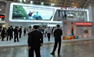 People visit Huawei Technologies booth display of its product during CommunicAsia 2010 conference and exhibtion show in Singapore. Chinese communications giant Huawei Technologies said it would invest $2.0 billion (1.5 billion euros) in Britain and roughly double its workforce in the country within five years