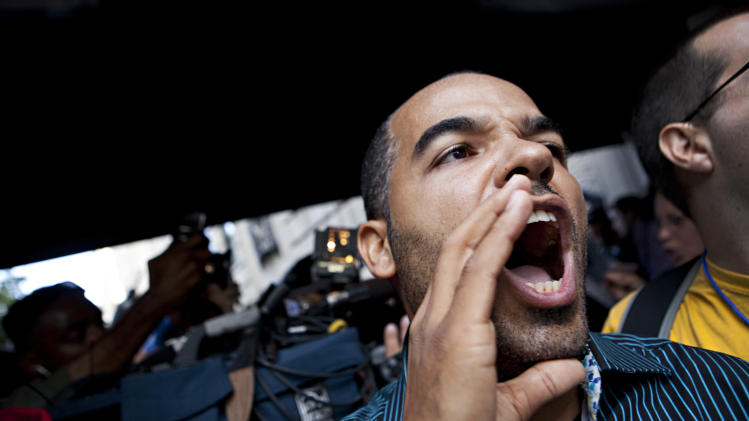 """A protestor affiliated with the """"Occupy Wall Street"""" protests chants outside 834 Fifth Avenue, where Rupert Murdoch lives, in New York, on Tuesday, Oct. 11, 2011. The crowd marched through out the Upper East Side neighborhood, protesting outside the homes of various billionaires and bank owners. (AP Photo/Andrew Burton)"""