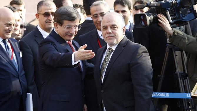 Turkey's Prime Minister Davutoglu gestures next to Iraqi Prime Minister al-Abadi as they attend a welcoming ceremony in Ankara