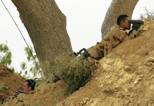 French foreign legionnaires take position outside Marakala, central Mali, some 240kms (140 miles) from Bamako Tuesday, Jan. 22, 2013. French troops in armored personnel carriers rolled through the streets of Diabaly on Monday, winning praise from residents of this besieged town after Malian forces retook control of it with French help a week after radical Islamists invaded. The Islamists also have deserted the town of Douentza, which they had held since September, according to a local official who said French and Malian forces arrived there on Monday as well. (AP Photo/Jerome Delay)