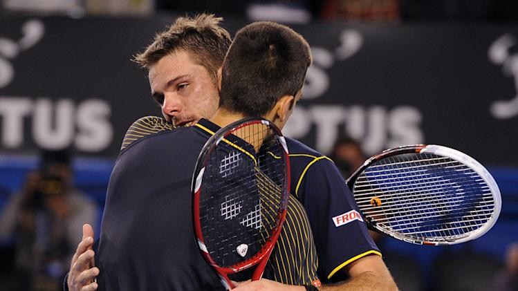 Serbia's Novak Djokovic embraces Switzerland's Stanislas Wawrinka, facing camera,  after Djokovic won their fourth round match at the Australian Open tennis championship in Melbourne, Australia, Sunday, Jan. 20, 2013.  (AP Photo/Andrew Brownbill)