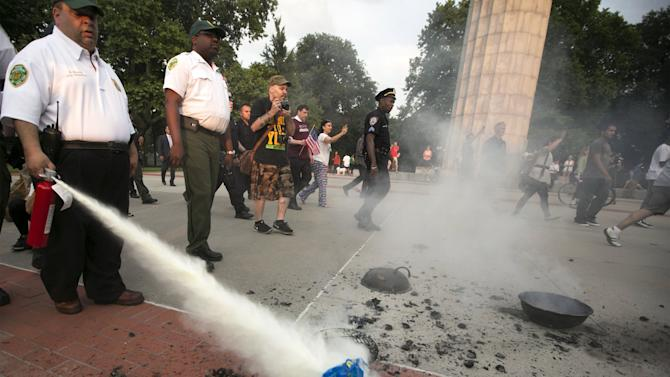New York City Parks Enforcement officers extinguish burning U.S. flag used for anti-police protest in Fort Green Park in Brooklyn Borough of New York