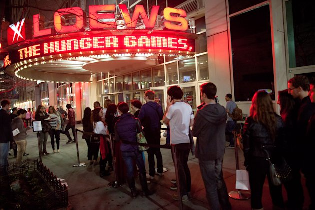 Fans line up to see the midnight shows of &quot;The Hunger Games,&quot; at the 34th Street Loews AMC Theatre, Thursday, March 22, 2012, in New York. The film, about children who are forced to compete in a live televised death match in the not-too-distant future, is based on the popular young adult book series by Suzanne Collins. (AP Photo/John Minchillo)